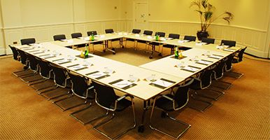 Image of a boardroom with a square table set out ready for a meeting