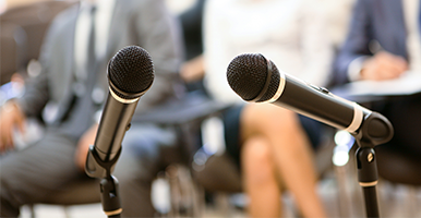 Image of two microphones on a podium with an audience in the background