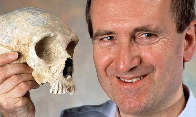 Image of Chris Stringer holding a skull.
