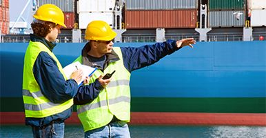 Image of two men at a dock wearing hard hats and high-vis jackets