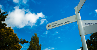 Image of sign pointing to the library with the sky as a backdrop