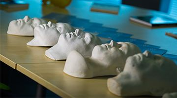 Image of sculpted faces laid out on a table