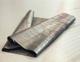 Roll of graphite paper laid out on a floor.