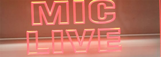 "Neon sign saying ""mic live"""