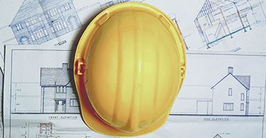 Builders hard hat on top of a map