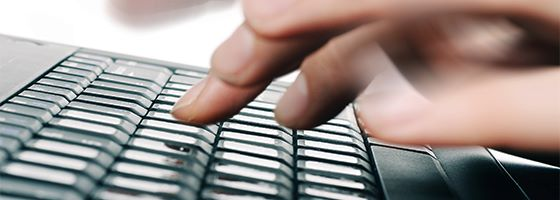 Close up shot of hands typing on a laptop