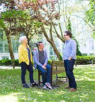 Image of three academic staff members in discussion outside the Aldham Robarts Library